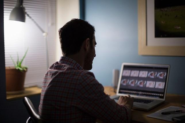 Man sitting at desk using laptop