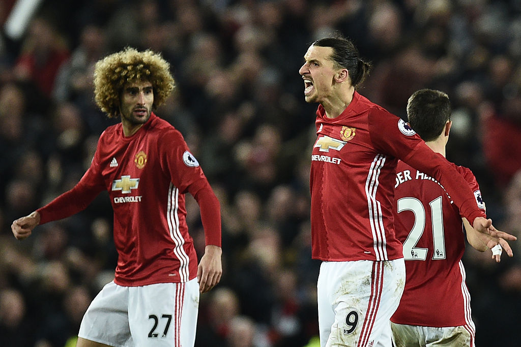 Manchester United's Swedish striker Zlatan Ibrahimovic (C) celebrates scoring his team's first goal with Manchester United's Belgian midfielder Marouane Fellaini (L) during the English Premier League football match between Manchester United and Liverpool at Old Trafford in Manchester, north west England, on January 15, 2017. The game finished 1-1. / AFP / Oli SCARFF / RESTRICTED TO EDITORIAL USE. No use with unauthorized audio, video, data, fixture lists, club/league logos or 'live' services. Online in-match use limited to 75 images, no video emulation. No use in betting, games or single club/league/player publications. / (Photo credit should read OLI SCARFF/AFP/Getty Images)