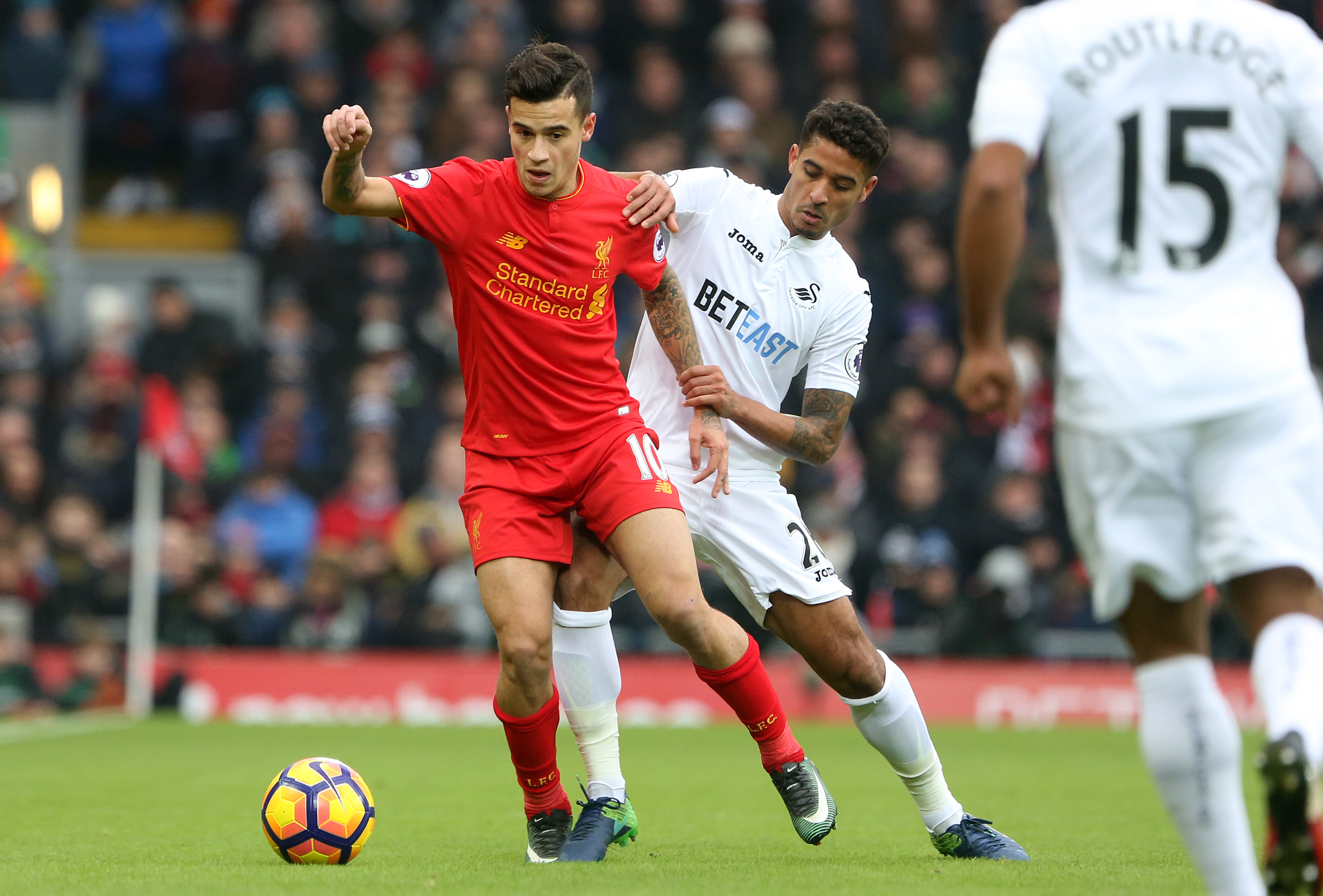 LIVERPOOL, ENGLAND - JANUARY 21: Philippe Coutinho of Liverpool is challenged by Kyle Naughton of Swansea City during the Premier League match between Liverpool and Swansea City at Anfield on January 21, 2017 in Liverpool, England. (Photo by Athena Pictures/Getty Images)