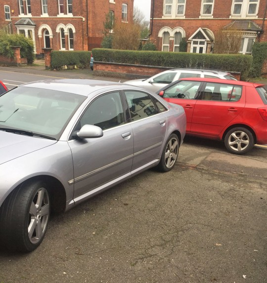 Pic from Caters News - Pictured: This bold motorist was left red-faced after parking on a strangers private driveway - and finding himself blocked in for two hours. The cheeky driver had parked his silver Audi over two spaces on a private drive - and when the occupant came back to find nowhere to park, they blocked him in. But when he came back to find the driver of the red Skoda nowhere to be found, he became furious and started bashing at the car, bouncing it up and down as he tried to push it out of the way with a pal. SEE CATERS COPY