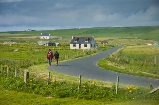 Orkney wants to leave the UK following Brexit People walking on the road in Scottish landscape in Orkney Island; Shutterstock ID 257976692