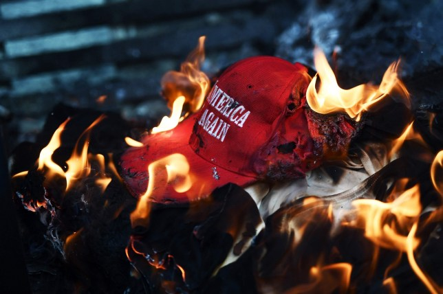"Anti-Trump demonstrator set a ""Make America Great Again"" hat on fire in Washington, DC, on January 20, 2107. Masked, black-clad protesters carrying anarchist flags smashed windows and scuffled with riot police Friday in downtown Washington, blocks away from the route of the parade in honor of newly sworn-in President Donald Trump. / AFP PHOTO / Jewel SAMADJEWEL SAMAD/AFP/Getty Images"