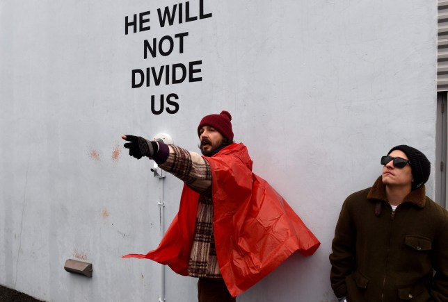 US actor Shia LaBeouf(L) during his He Will Not Divide Us livestream outside the Museum of the Moving Image in Astoria, in the Queens borough of New York January 24, 2017 as a protest against President Donald Trump. LaBeouf has installed a camera at the Museum of the Moving Image in New York that will run a continuous live stream for the duration of Trumps presidency. LaBeouf is inviting the public to participate in the project by saying the phrase, He will not divide us, into the camera. / AFP PHOTO / TIMOTHY A. CLARYTIMOTHY A. CLARY/AFP/Getty Images