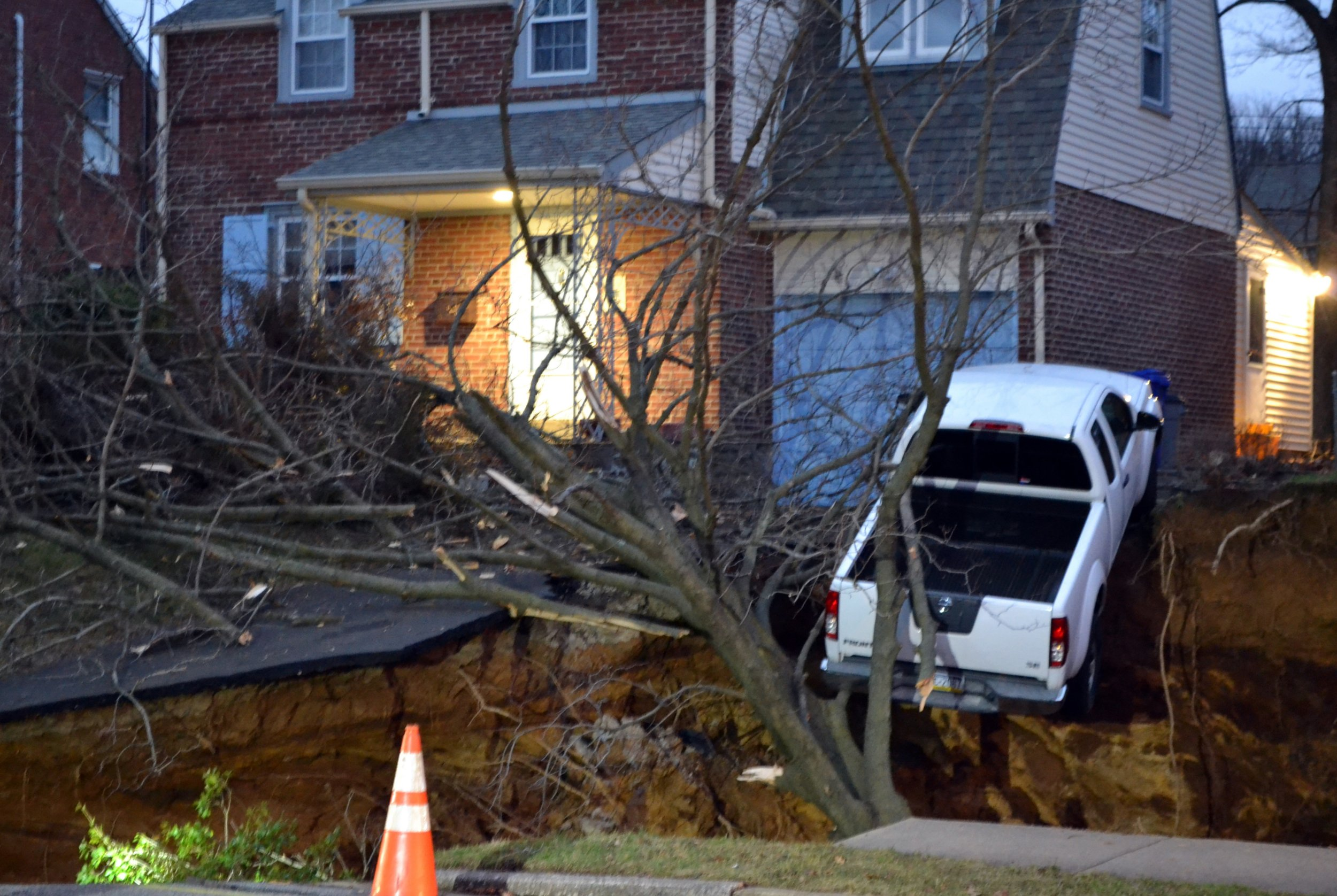 A pickup truck dangles over the edge of a sinkhole the swallowed parts of two residential yards Wednesday morning, Jan. 25, 2017, in the Philadelphia suburb of Glenside, Pa. Officials in Cheltenham Township say the hole, which appears to be about 20 feet deep, opened up about 4 a.m. Wednesday. Authorities say nobody's been hurt and there was no obvious, immediate cause for the sinkhole to develop. (Emily Casher Loomis via AP)