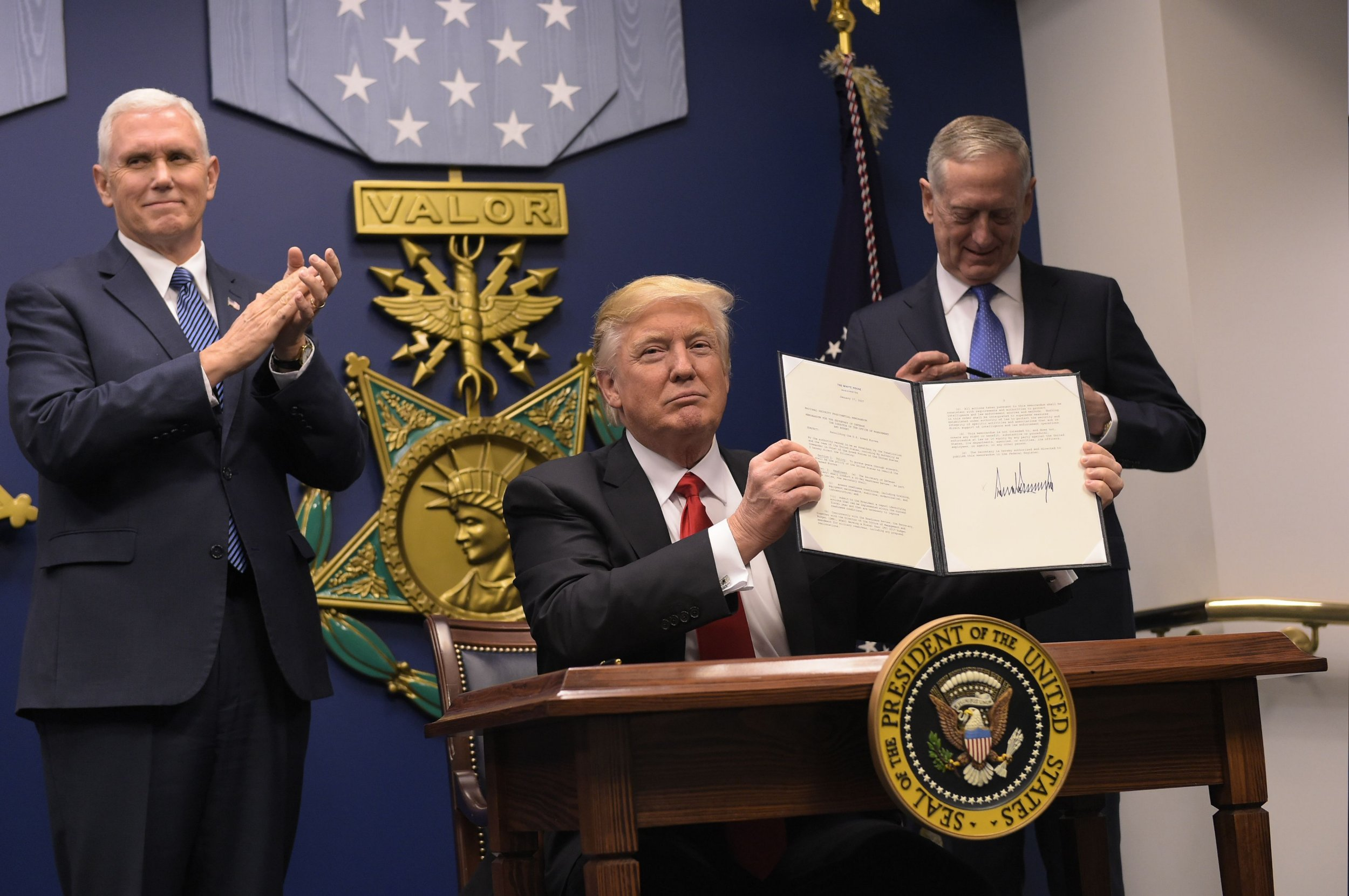 """US President Donald Trump shows his signature on executive orders alongside US Defense Secretary James Mattis and US Vice President Muike Pence on January 27, 2016 at the Pentagon in Washington, DC. Trump signed an order Friday to begin what he called a """"great rebuilding"""" of the US armed services, promising new aircraft, naval ships and more resources for the military. """"Our military strength will be questioned by no one, but neither will our dedication to peace. We do want peace,"""" Trump said in a ceremony at the Pentagon. / AFP PHOTO / MANDEL NGANMANDEL NGAN/AFP/Getty Images"""