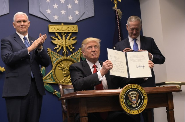 "US President Donald Trump shows his signature on executive orders alongside US Defense Secretary James Mattis and US Vice President Muike Pence on January 27, 2016 at the Pentagon in Washington, DC. Trump signed an order Friday to begin what he called a ""great rebuilding"" of the US armed services, promising new aircraft, naval ships and more resources for the military. ""Our military strength will be questioned by no one, but neither will our dedication to peace. We do want peace,"" Trump said in a ceremony at the Pentagon. / AFP PHOTO / MANDEL NGANMANDEL NGAN/AFP/Getty Images"