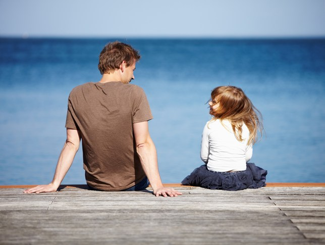Rear-view of a young father and his daughter sitting on a pier with the ocean in the background