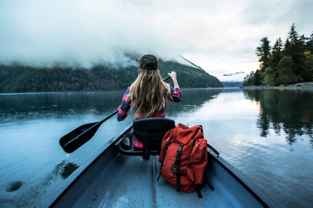 A woman paddling a canoe across a lake early in the morning.