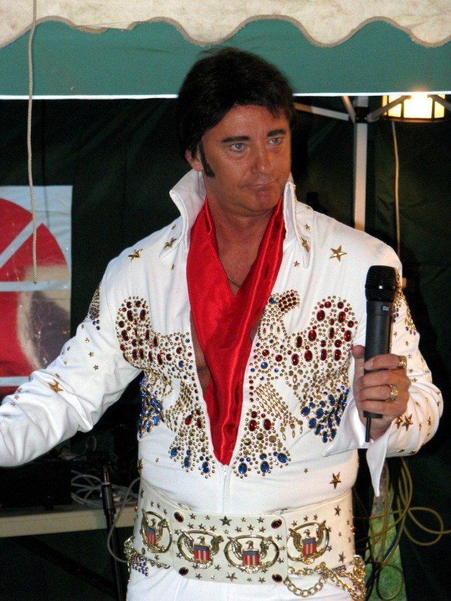 Christopher Martin Burrows performing as Elvis. See NTI story NTIELVIS; An Elvis impersonator stole a cancer charity collection at his mother-in-law's FUNERAL  - after performing a tribute song as The King, a court heard. Christopher Martin Burrows, 56, sang 'The Wonder Of You' during the service in memory of his then wife's mother Solange Scott. But a court heard just minutes later he pocketed £290 which had been collected by mourners for Macmillan Cancer Support on October 27, 2015. Burrows, of Wigston, Leics., denied a charge of theft when he went on trial at Leicester Crown Court on Thursday (23/2). Jurors were told the Elvis tribute act is known for his renditions of songs by the legendary singer at functions across the country.