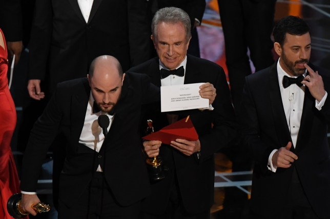 """US actor Warren Beatty (C) shows the card reading Best Film 'Moonlight"""" after mistakingly reading """"La La Land"""" initially at the 89th Oscars on February 26, 2017 in Hollywood, California. / AFP PHOTO / Mark RALSTONMARK RALSTON/AFP/Getty Images"""
