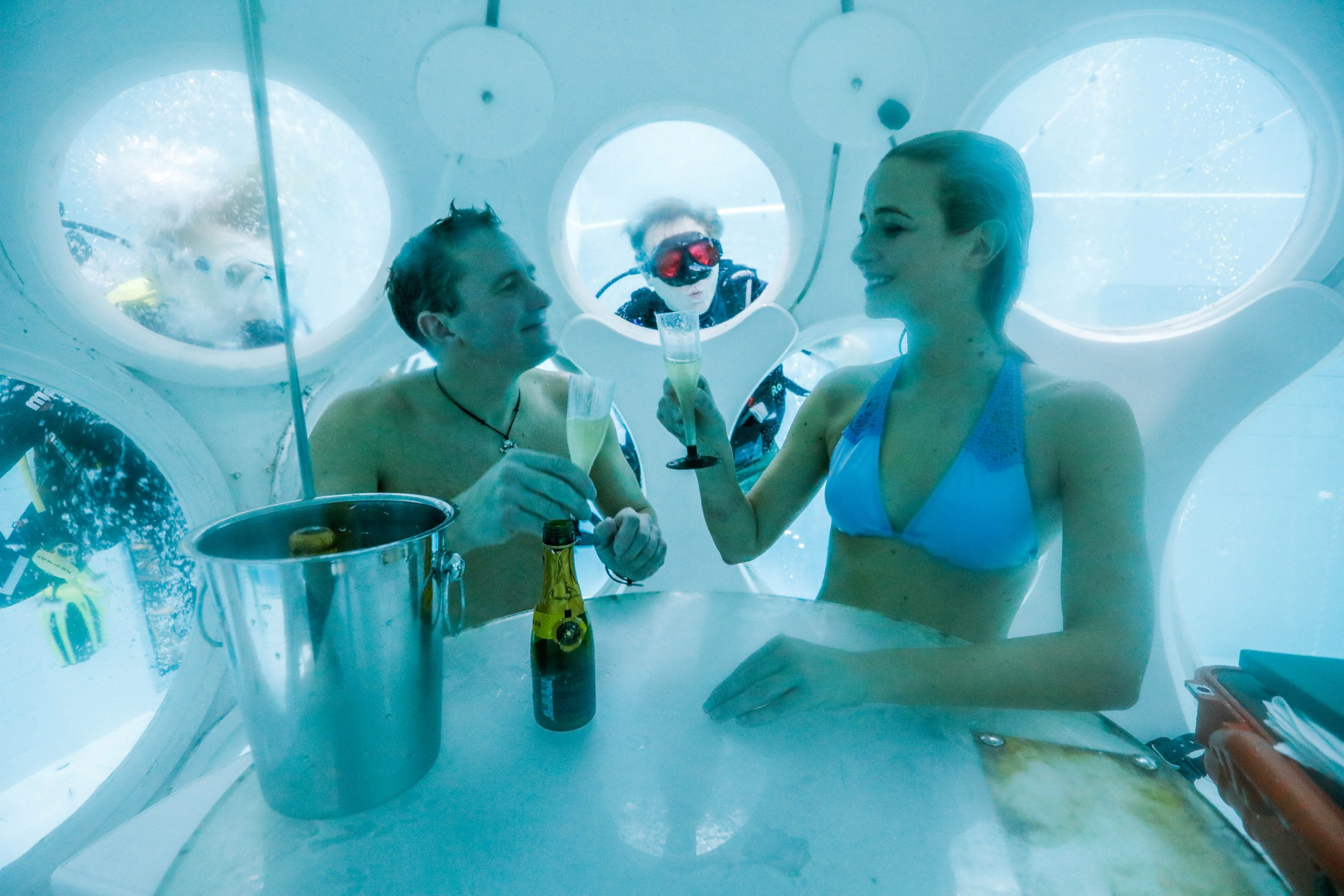 """Belgians Florence Lutje Spelberg and Nicolas Mouchart drink champagne while sitting inside """"The Pearl"""", a spheric dining room placed 5 metres underwater in the NEMO33 diving center, one of the world's deepest pools (33 metre/36 yards) built to train professional divers, before enjoying a meal inside, in Brussels, Belgium January 30, 2017. Picture taken January 30, 2017 REUTERS/Yves Herman"""
