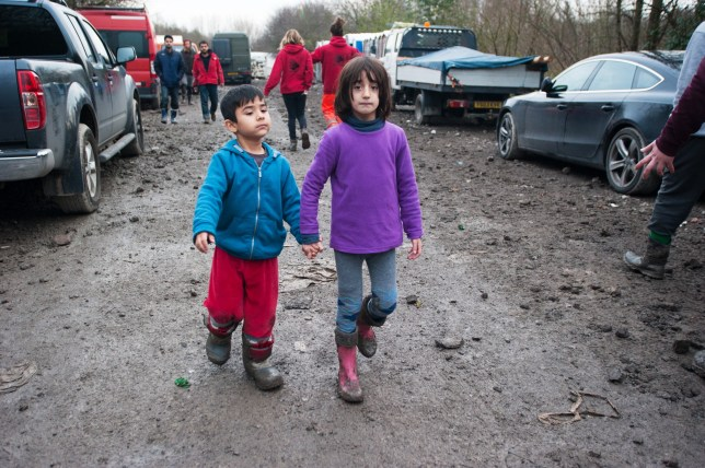 Child refugees (Getty) DUNKIRK, FRANCE - 2015/12/17: Two refugee children are walking hand in hand through the refugee camp in Dunkirk. Still more than 2000, mostly Kurdish refugees are staying temporarily at an illegal refugee camp in Dunkirk, waiting to travel to the UK. Random lock-downs by the police, mud, cold and prevalent trash problems make life hard in this camp. (Photo by Frederik Sadones/Pacific Press/LightRocket via Getty Images)
