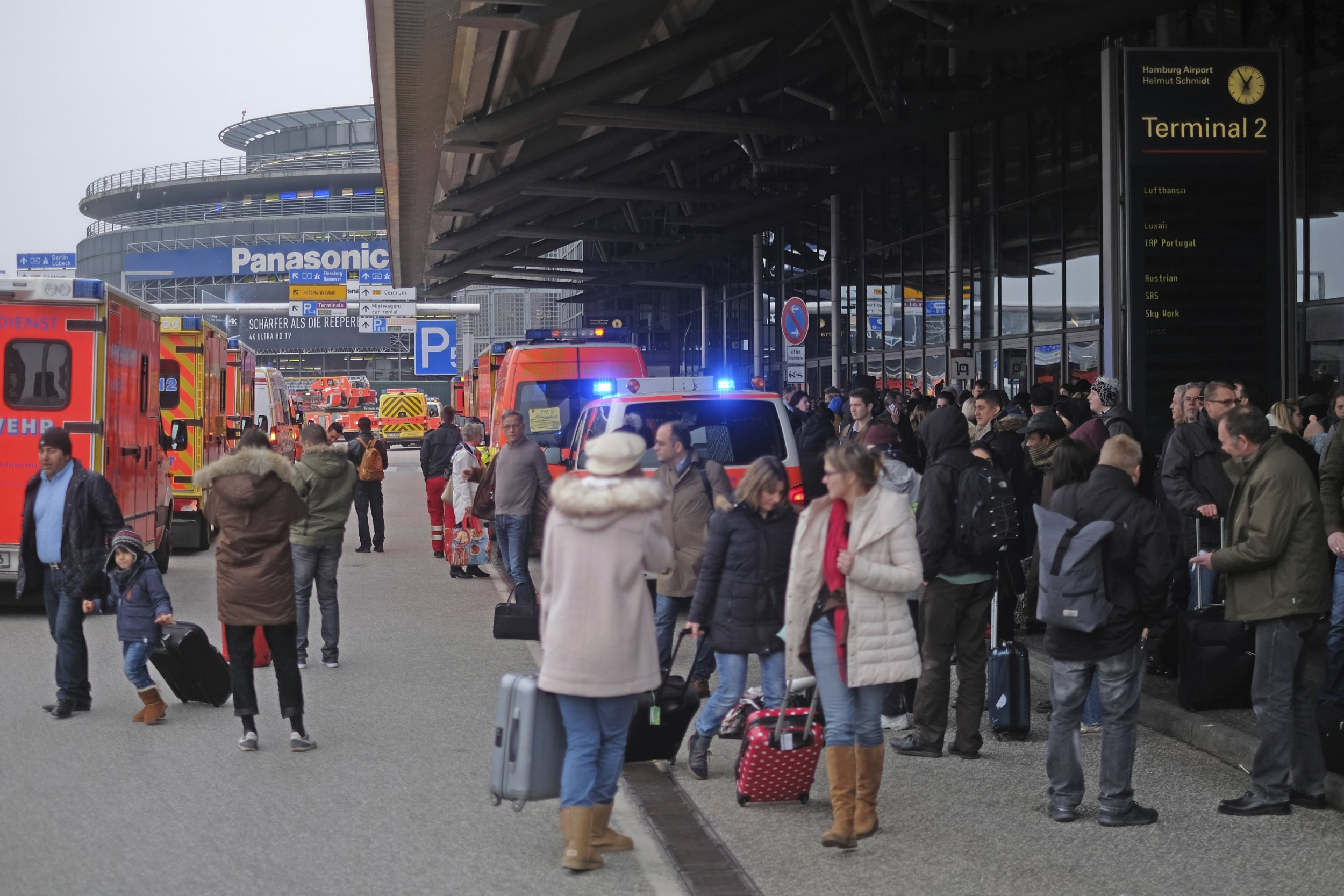 Travellers wait outside the Hamburg, northern Germany, airport Sunday, Feb. 12, 2017 after after several people were injured by an unknown toxic that likely spread through the airportsí air conditioning system. (Axel Heimken/dpa via AP)