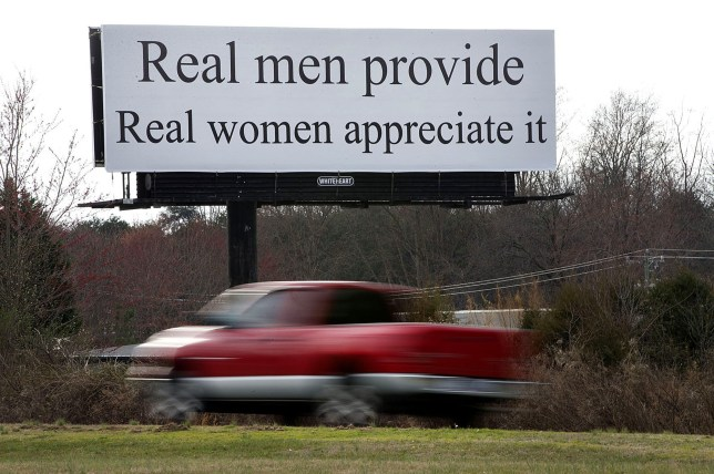 "A vehicle drives by a billboard, Wednesday, Feb. 22, 2017, near Greensboro, N.C. The billboard on a highway between Winston-Salem and Greensboro reads, ""Real men provide. Real women appreciate it."" Women are planning this weekend to protest a North Carolina billboard with a message they say is a slam on gender equality, according to media reports. (Andrew Krech/News & Record via AP)/"