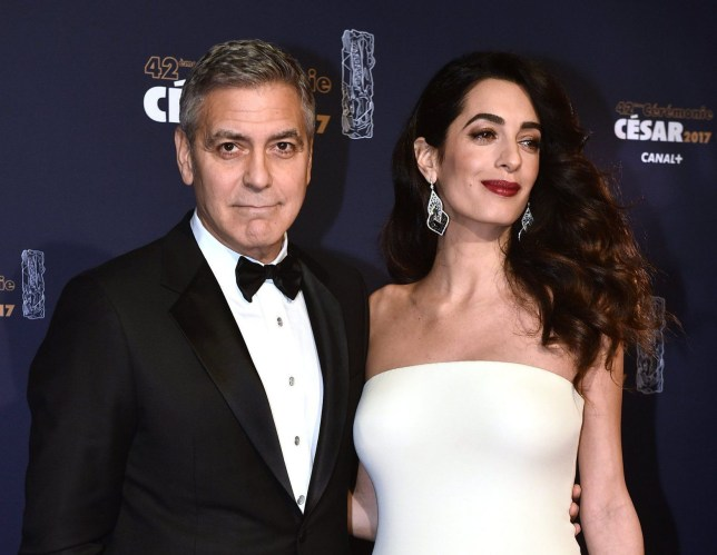 epa05813445 US actor George Clooney (L) and his wife Amal Clooney (R) arrive for the 42nd annual Cesar awards ceremony held at the Salle Pleyel concert hall in Paris, France, 24 February 2017. EPA/CHRISTOPHE PETIT TESSON