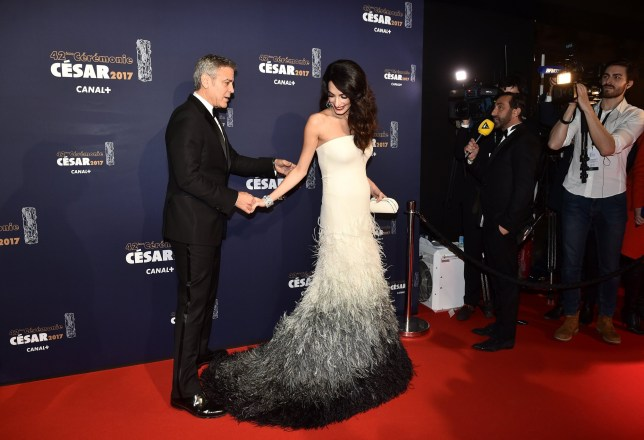 epa05813447 US actor George Clooney (L) and his wife Amal Clooney (R) arrive for the 42nd annual Cesar awards ceremony held at the Salle Pleyel concert hall in Paris, France, 24 February 2017. EPA/CHRISTOPHE PETIT TESSON