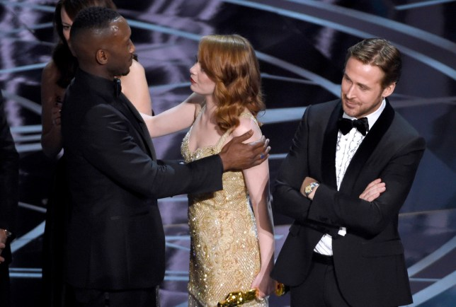 "Ryan Gosling, right, stands with his arms folded as Emma Stone, center, congratulates Mahershala Ali, for winning the award for best picture for ""Moonlight"" at the Oscars on Sunday, Feb. 26, 2017, at the Dolby Theatre in Los Angeles. It was originally announced mistakenly that ""La La Land"" was the winner. (Photo by Chris Pizzello/Invision/AP)"