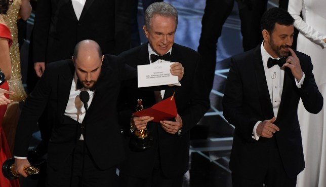 "US actor Warren Beatty (C) shows the card reading Best Film 'Moonlight"" next to ""La La Land"" producer Jordan Horowitz (L) and host Jimmy Kimmel after mistakingly reading ""La La Land"" initially at the 89th Oscars on February 26, 2017 in Hollywood, California. / AFP PHOTO / Mark RALSTONMARK RALSTON/AFP/Getty Images"