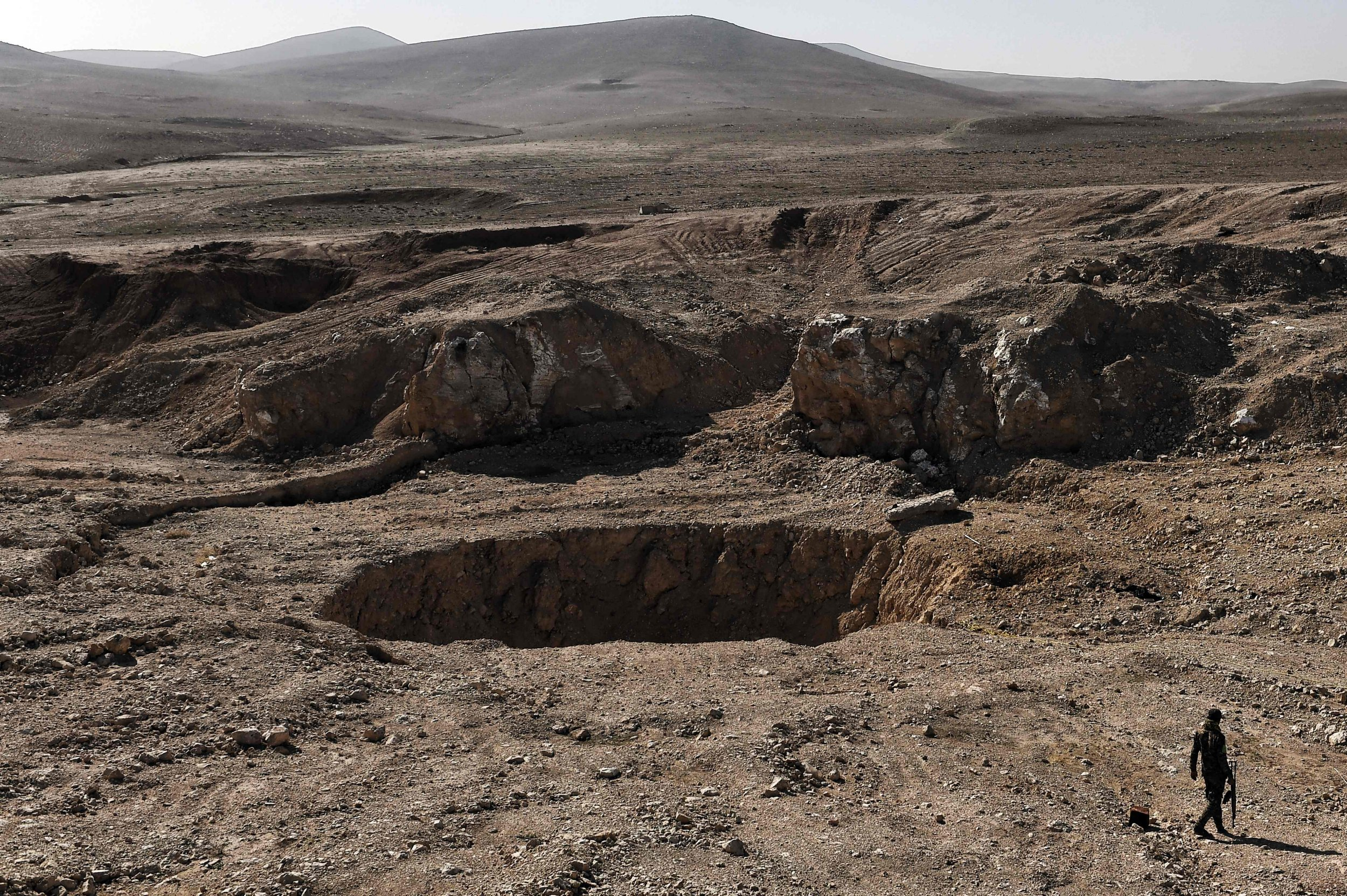 A member of the Hashed al-Shaabi (Popular Mobilisation) paramilitaries, walks next to a sinkhole, known as the Khasfah (an Arabic word for a crack or a hole that opens up in the ground), in the village of Athbah, south of Mosul on February 26, 2017. / AFP PHOTO / ARIS MESSINISARIS MESSINIS/AFP/Getty Images