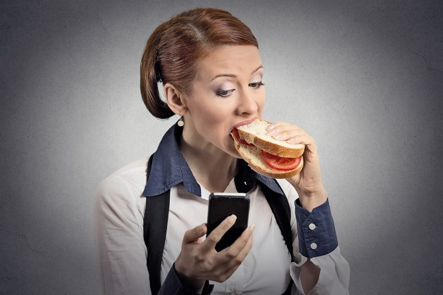 (Picture: Shutterstock) Closeup portrait young serious corporate business woman deal maker reading news message on smart mobile phone holding eating sandwich isolated grey background. Human face expression. Social media app; Shutterstock ID 223150447