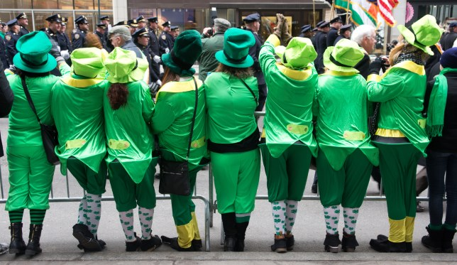 people in leprechaun costumes, lined up along the route of the St. Patrick's Day Parade in New York City.