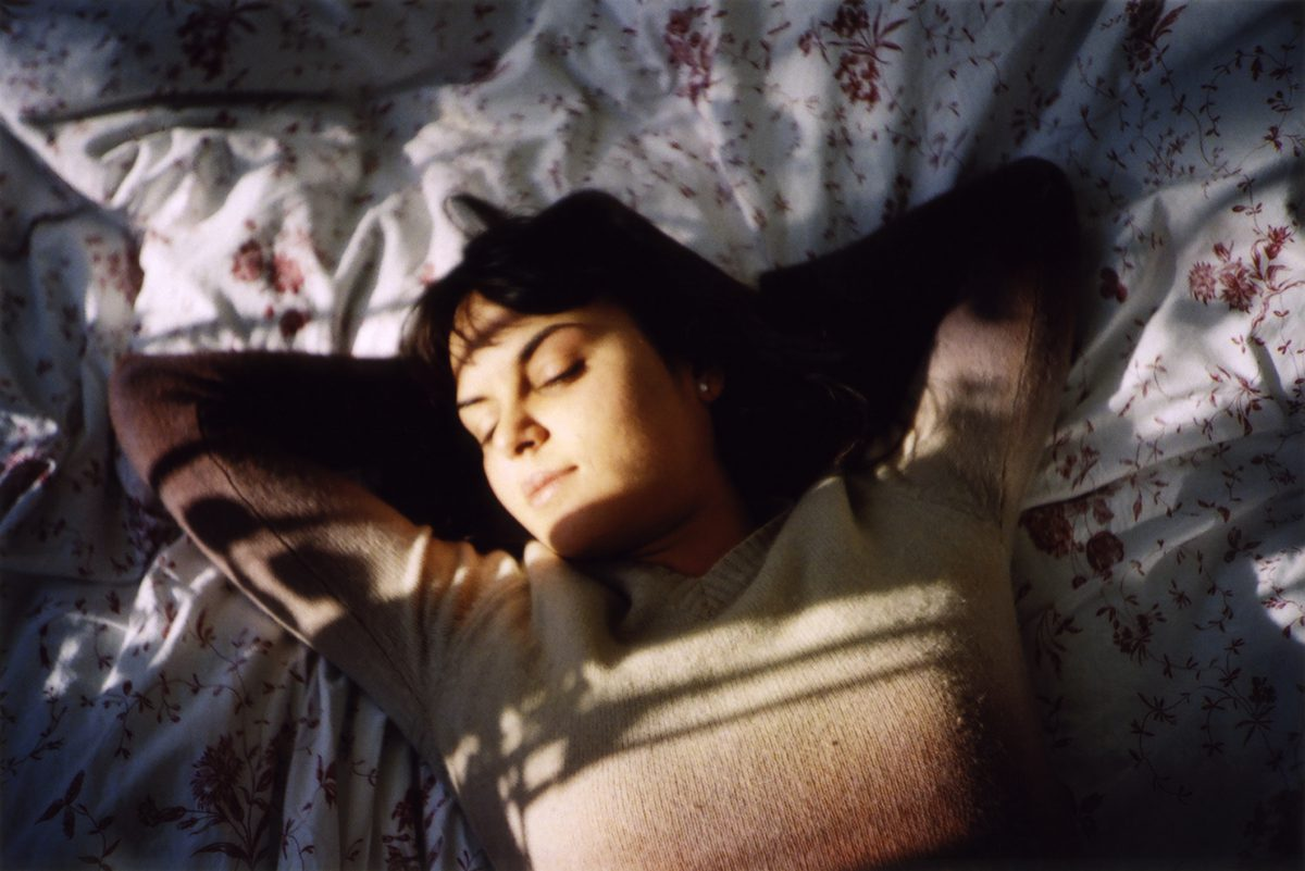 Girl taking a nap on the bed with brown sweater.