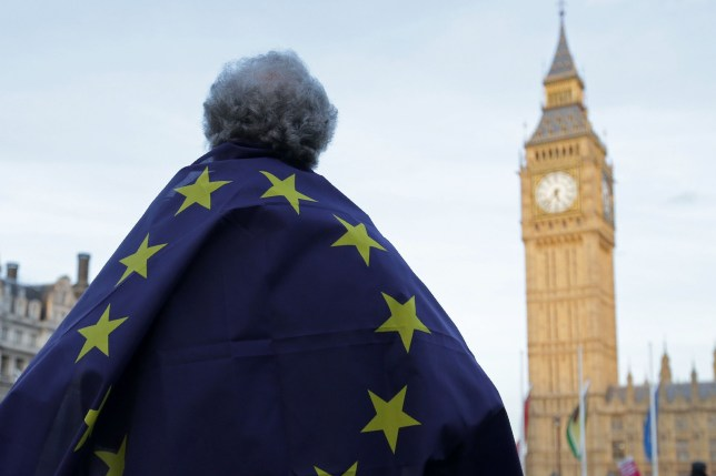 A protester draped in a European Union flag takes part in a protest in support of an amendment to guarantee legal status of EU citizens, outside the Houses of Parliament in London on March 13, 2017. British Prime Minister Theresa May feared parliament would stand in her way in implementing Brexit but the opposition crumbled and she prepares to open negotiations with the wind in her sails. / AFP PHOTO / Daniel LEAL-OLIVASDANIEL LEAL-OLIVAS/AFP/Getty Images
