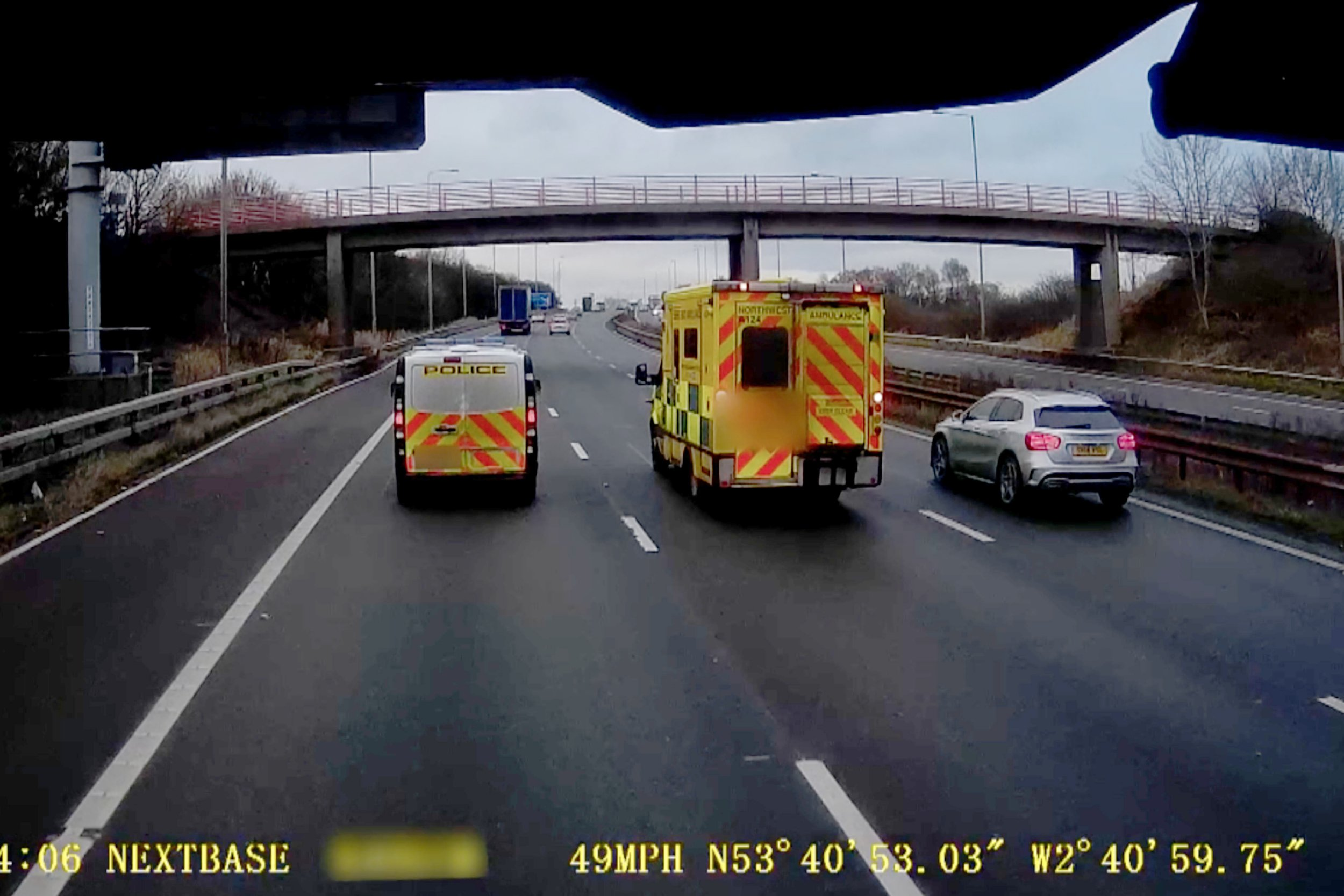 PIC FROM MERCURY PRESS (PICTURED: THE DRIVERS OF THE TWO EMERGENCY VEHICLES APPEAR TO BE TALKING TO EACH OTHER ON THE LEYLAND STRETCH OF M6 MOTORWAY IN LANCASHIRE) This is the moment a police van and an ambulance slowed down ëdangerouslyí to just 32mph on a busy motorway so the drivers could have a CHAT through the window, a fellow motorist claims. Lorry driver Ian Price said he was stunned as the two vehicles hit the brakes and began 'crawling' along the northbound M6 in Lancashire. The emergency services, who were occupying lanes one and two of the motorway, didnít have their flashing lights on and travelled at just half the road's speed limit near junction 28 in Leyland. SEE MERCURY COPY