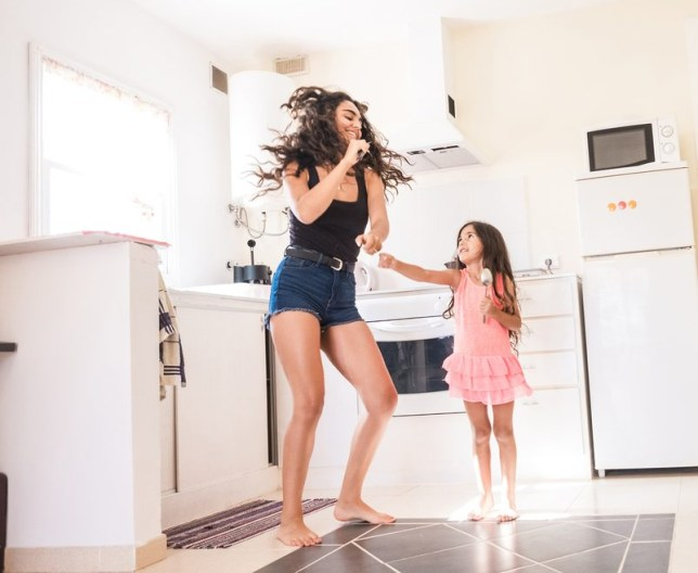 Playful teenage girl with her little sister in kitchen