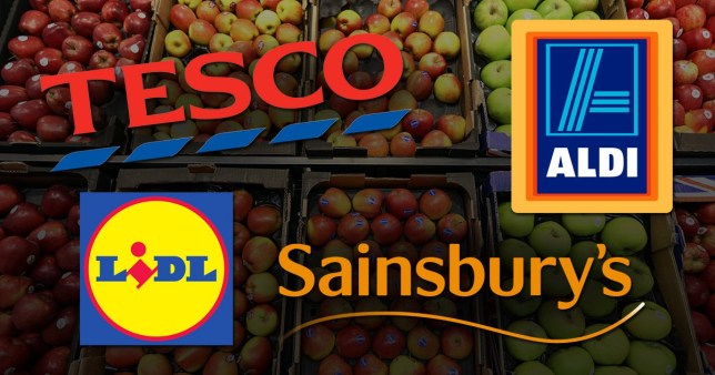 Logos for Tesco, Lidl, Sainsburys and Aldi in front of apples on display at a supermarket