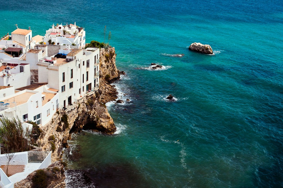 Houses perched on rocks above sea in Ibiza town