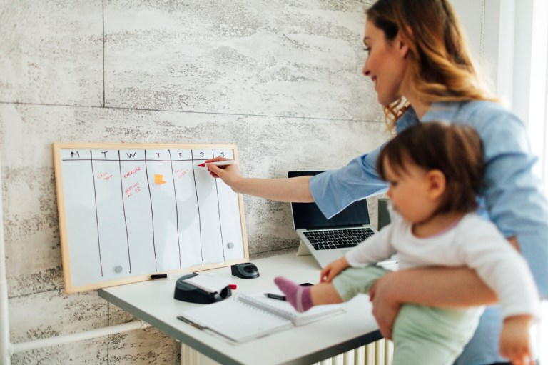 Mother working from home while carrying her cute baby girl. She is writing on whiteboard, entering into the schedule. She is happy and cheerful. Mother is working from home.