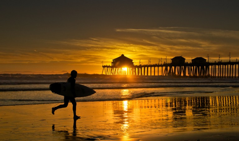 A silhouette of a male surfer running to catch the last waves of the day at Sunset at Southern California's Huntington Beach. The Wharf is in the background