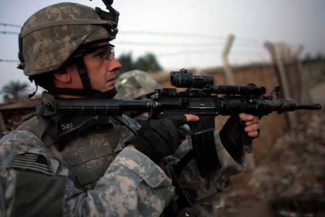 A sniper with the army seen looking through lense of gun in camo gear