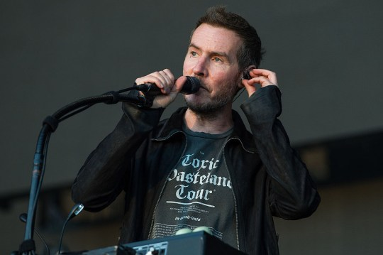 Robert Del Naja of the band Massive Attack performing on stage, with a microphone to his lips and holding a headphone to his ear