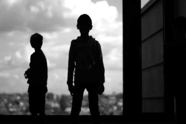 boys standing against a sky background