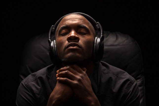 Portrait of a young man of African descent with his eyes closed focused intensely on listening to music with large headphones