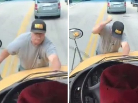 Angry man hangs onto front of moving school bus to shout at students