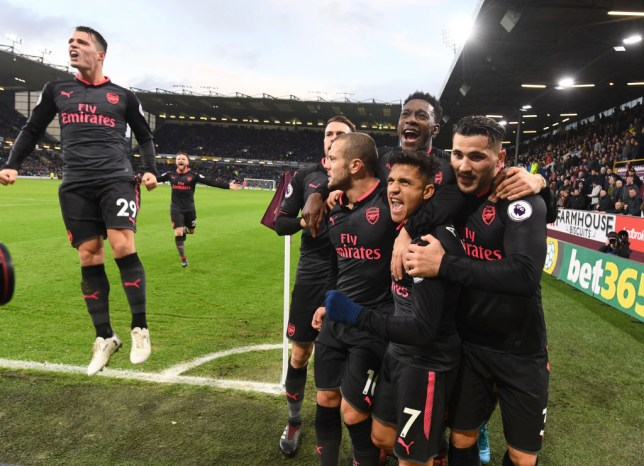Alexis Sanchez is mobbed by his team-mates as Granit Xhaka leaps in the air
