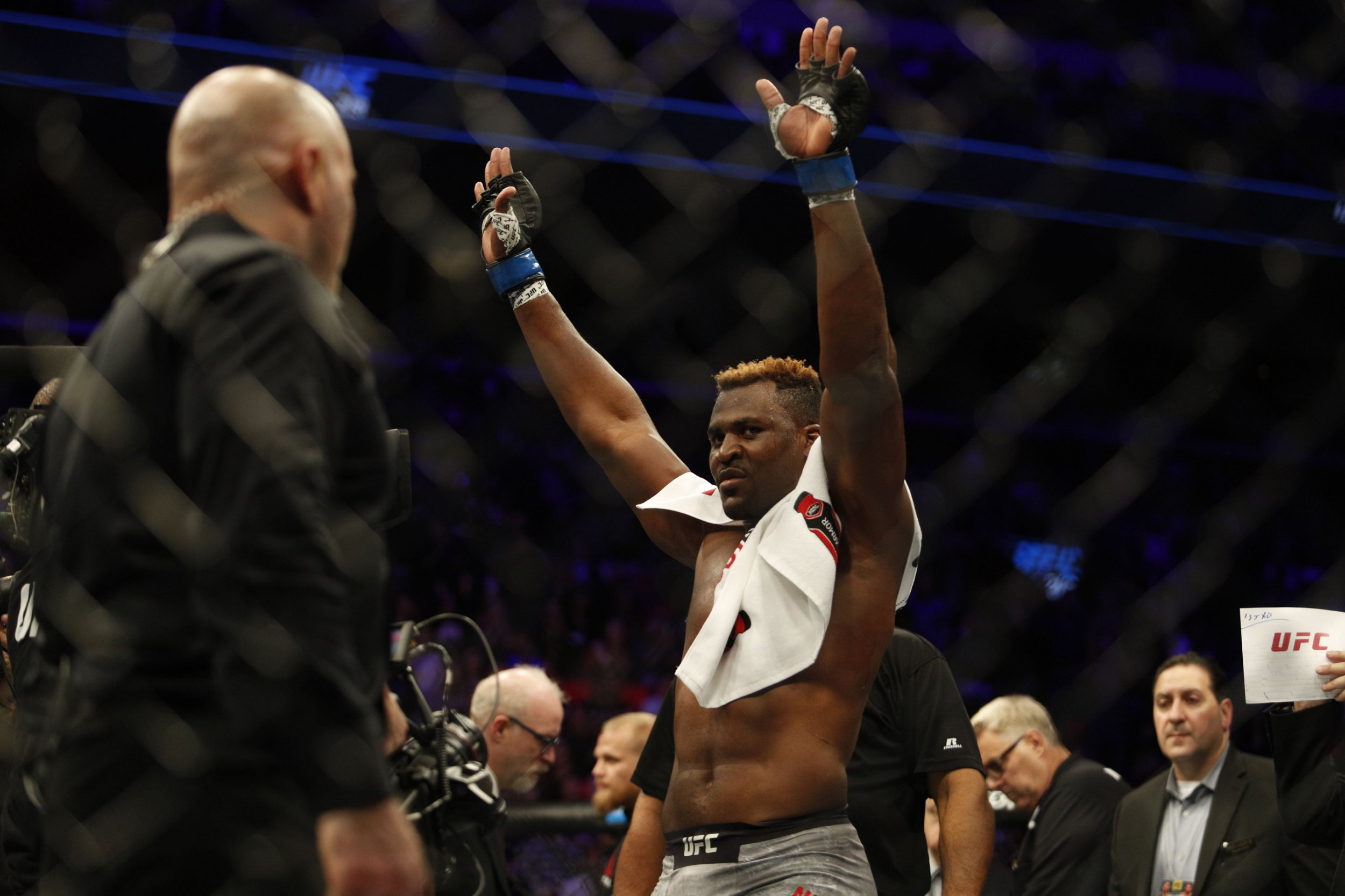 Francis Ngannou celebrates with his hands in the air and a towel round his neck