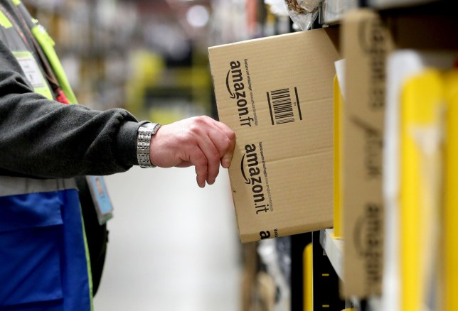 Staff make their way around the aisles collecting items before sending them to the on-site dispatch hall to be packaged inside one of Britain's largest Amazon warehouses in Dunfermline, Fife, as the online shopping giant gears up for the Christmas rush and the forthcoming Black Friday sales.