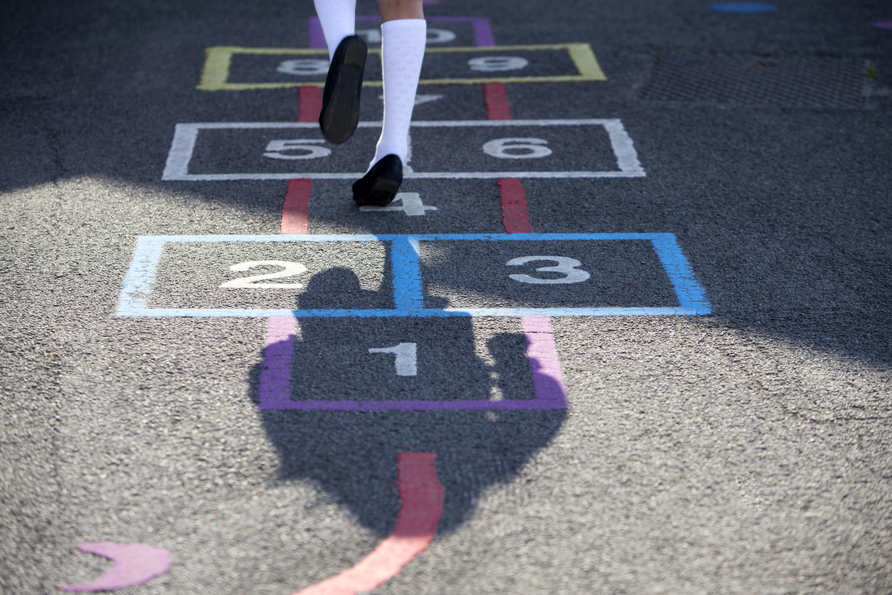 Picture of a schoolgirl playing hopscotch in the playground. Only seen from below the waist