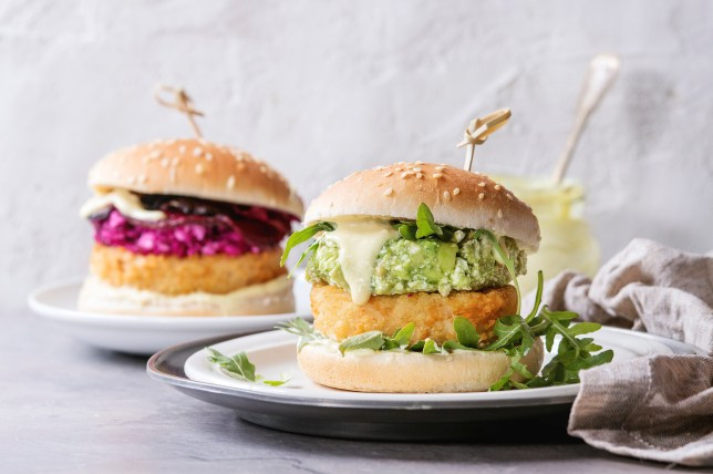 Two vegetarian hamburgers with onion and cheese cutlets, avocado salad, arugula, fried beetroot and yogurt sauce in white plate over gray texture background. Healthy fast food.