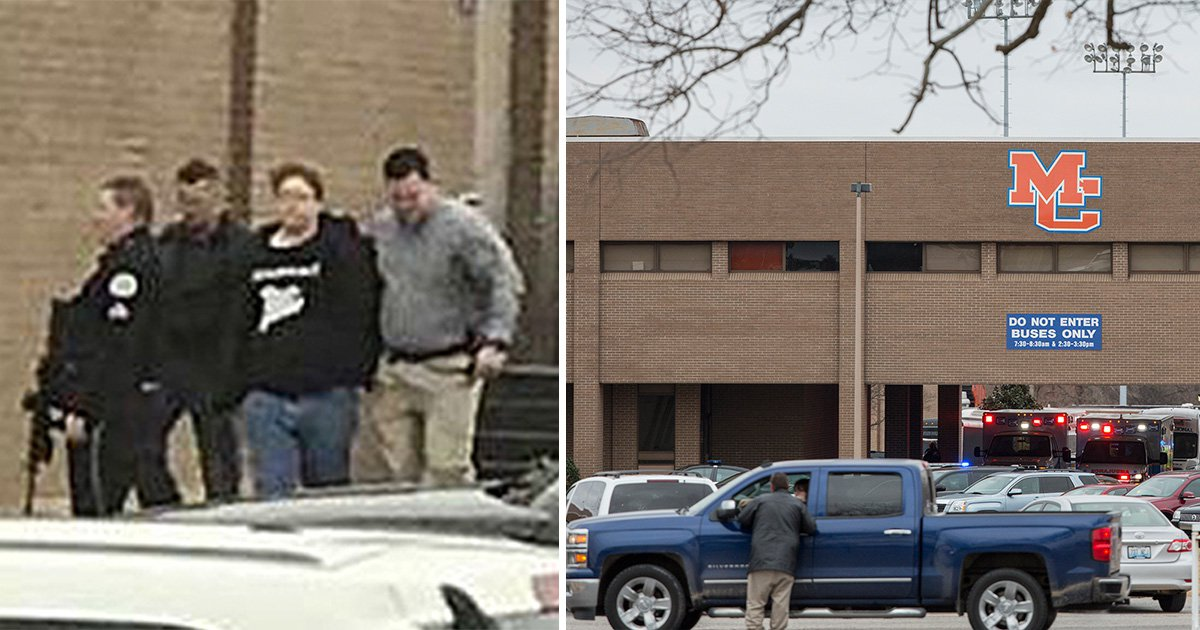 Boy, 15, led away in handcuffs after two students are shot dead and 19 others are injured at school