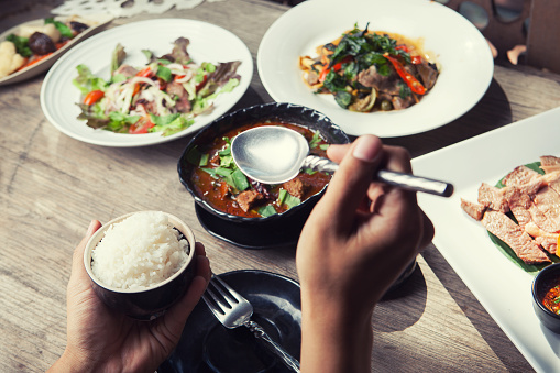 hand holding spoon and dinner with Thailand food hot and spicy with herb on wooden table