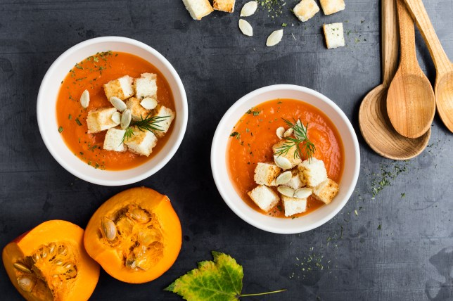 Butternut squash cream soup in bowl with croutons on dark background, traditional autumn dish on rustic table viewed from above