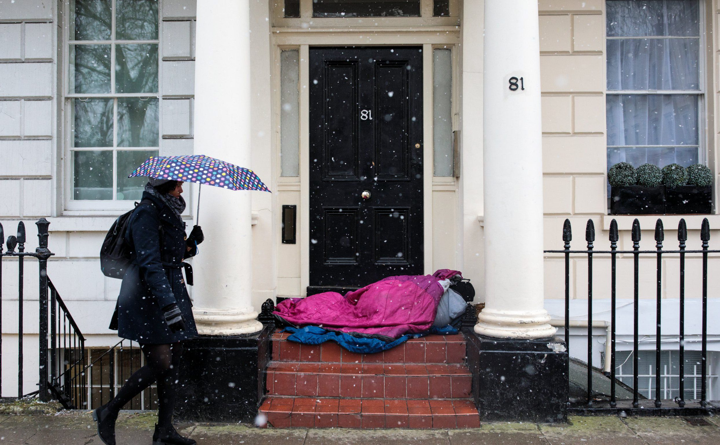 "LONDON, ENGLAND - FEBRUARY 26: A woman carrying an umbrella walks past a homeless person sleeping in a doorway during a snow shower on February 26, 2018 in London, United Kingdom. Freezing weather conditions dubbed the ""Beast from the East"" brings snow and sub-zero temperatures to the UK. (Photo by Jack Taylor/Getty Images)"