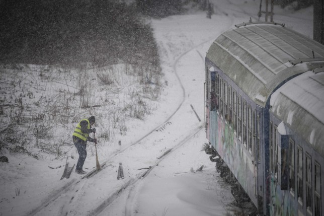 A worker removes snow from a railway switch point close to the North Station in Bucharest on February 27, 2018. Romania's National Railway Company (CFR) canceled 120 trains following severe weather and cold that strikes Romania during the past two days. The Romanian National Weather Institute issued an orange code for low temperature for the next two days as they expected lows that will reach -22 degrees Celsius, according to the forecasst. / AFP PHOTO / Daniel MIHAILESCUDANIEL MIHAILESCU/AFP/Getty Images