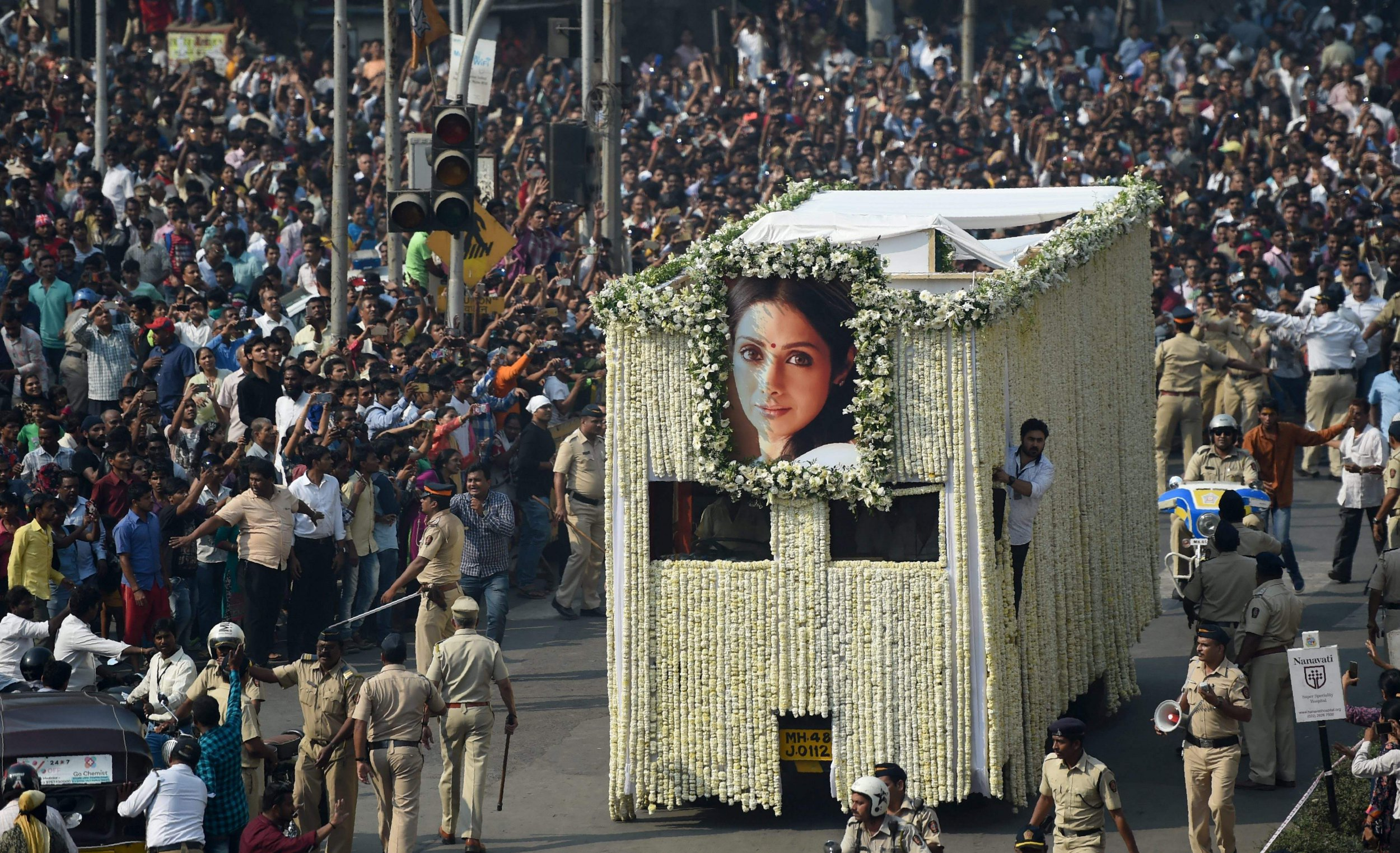 Indian fans watch as the funeral cortege of the late Bollywood actress Sridevi Kapoor passes through Mumbai on February 28, 2018. Thousands of heartbroken fans lined the streets of Mumbai February 28 as India said farewell to Bollywood legend Sridevi Kapoor following her shock death from accidental drowning in a Dubai hotel bathtub aged just 54. / AFP PHOTO / PUNIT PARANJPEPUNIT PARANJPE/AFP/Getty Images