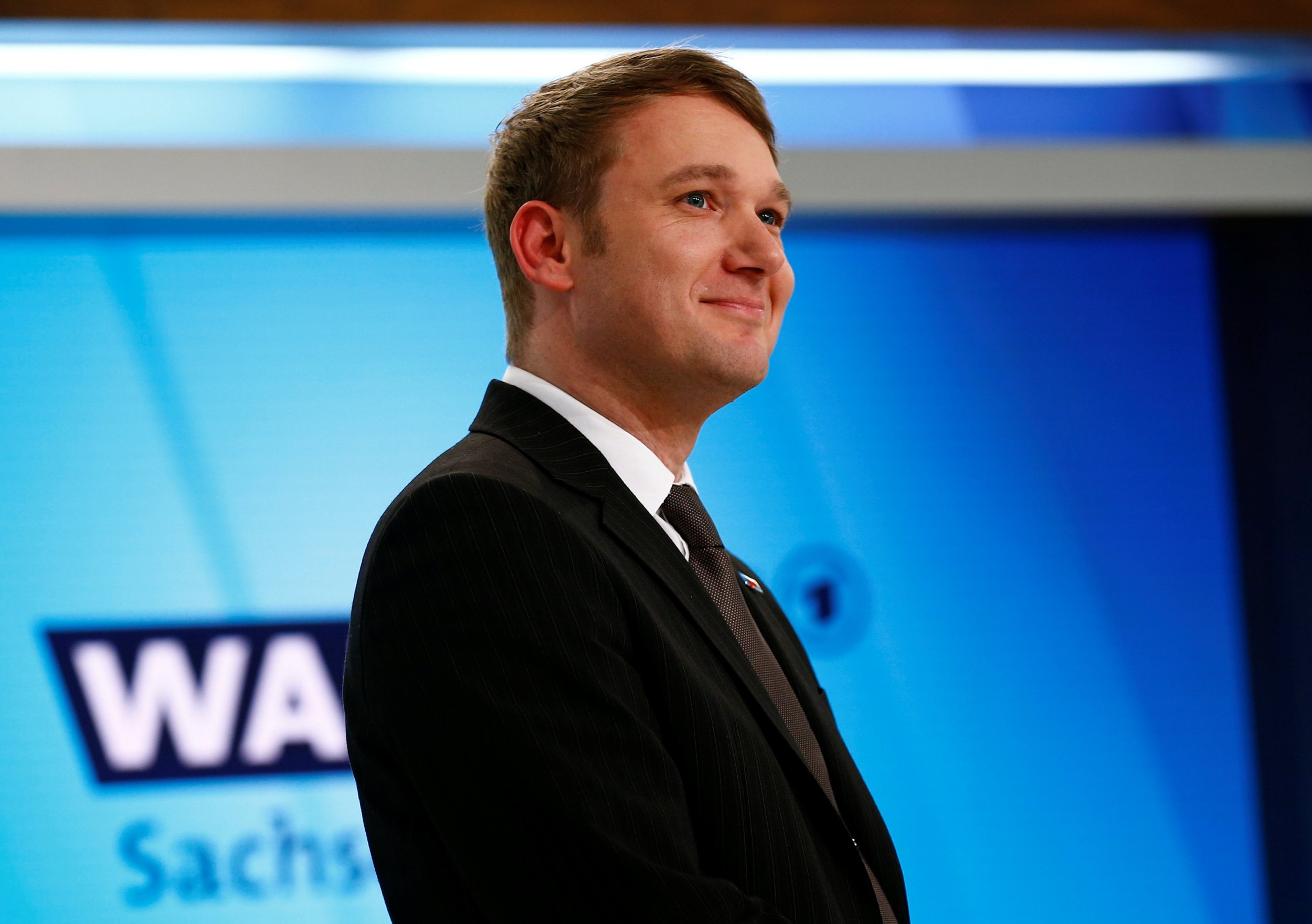 FILE PHOTO: Andre Poggenburg of the anti-immigration Alternative for Germany (AfD) party smiles during TV interview after the first local elections polls in Magdeburg, Germany March 13, 2016. REUTERS/Wolfgang Rattay/File Photo